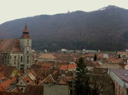 """Old town and mountain with the """"Brasov"""" sign on top, resembling """"Hollywood"""" letters"""