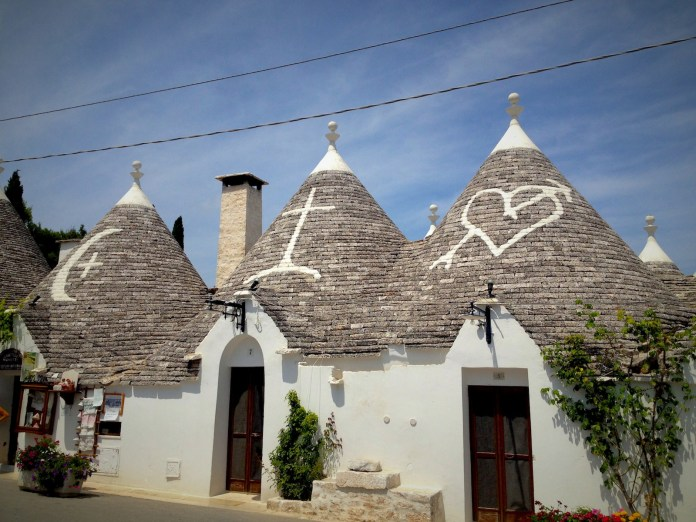 The conical trulli roofs are decorated with various spiritual characters