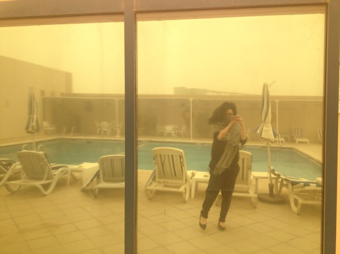 Me in Abu Dhabi, facing the sandstorm on the hotel's roof