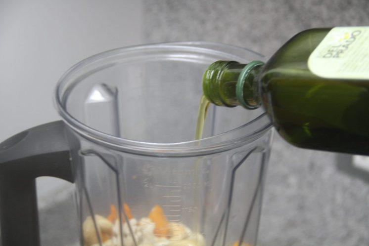 La salsa huancaína se preparara súper simple: en la licuadora o procesador de alimentos, agregar el aceite de oliva, cashews, ajíes, agua y sal.