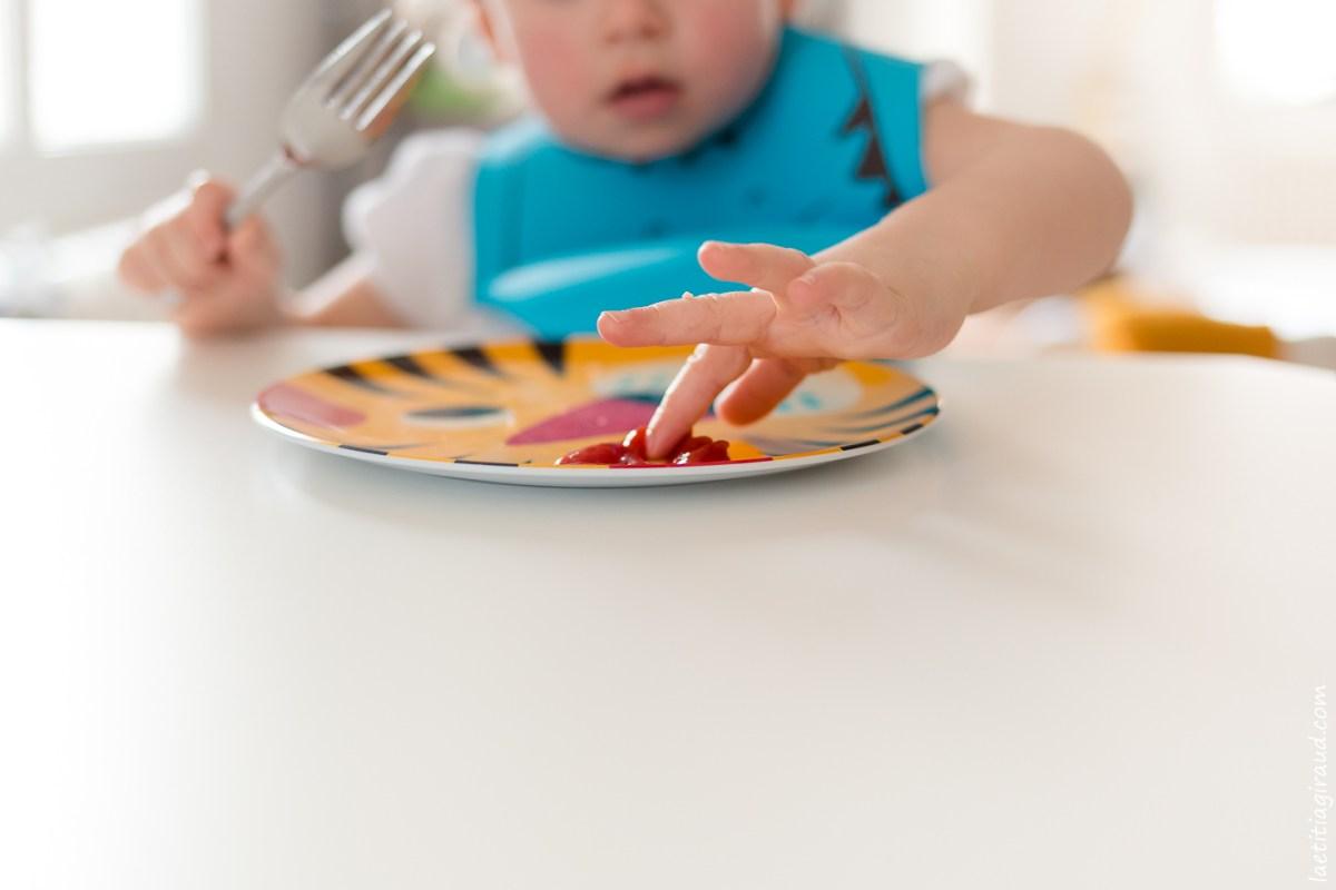 petite fille qui mange avec les mains
