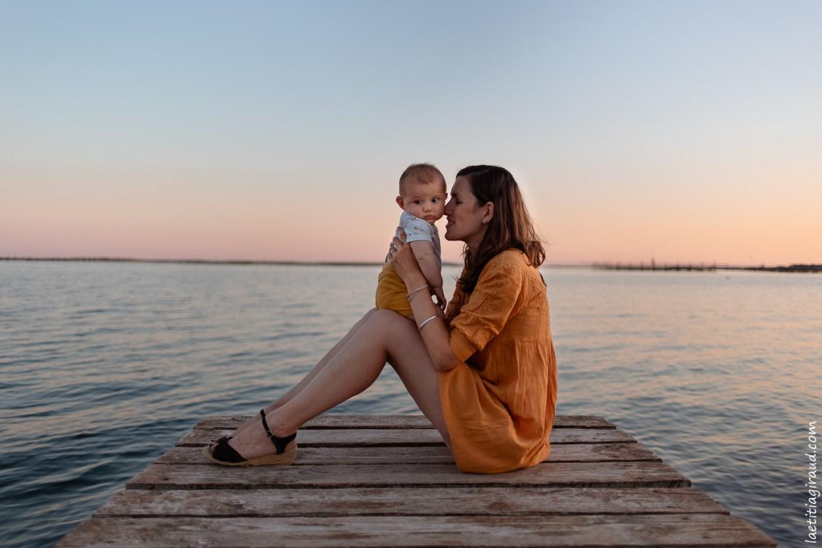 maman sur un ponton a la mer avec son bebe contre elle