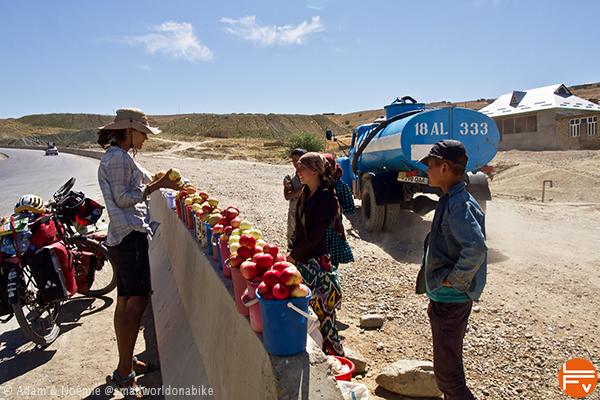 Noémie achète des pommes au bord de la route, en plein désert ouzbèque