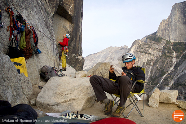 A climber reads the guidebook, sitting at the start of a route. Another guy belay a climber