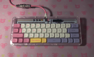pastel themed mini keyboard. the letter keys are white, alt/ctrl/shift keys are light pink and light purple. The keyboard rests on a pink table with cute animal silhouettes on it.