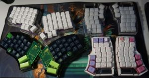 various split keyboard designs. There are four in total. Upper left is a clear acrylic keyboard with white buttons. Upper right is a clear split keyboard with clouded keys. Lower left is a black split keyboard with neon green keys. Lower right is a white split keyboard with purple, pink, and white keys