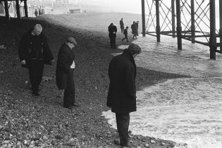 Blacksanding. Sunday morning men gather under Brighton pier, waiting for money to be washed up with the tide. Brighton, Sussex, 1970. ©Homer Sykes/Courtesy Les Douches la Galerie