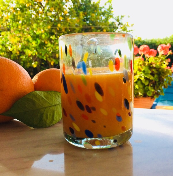 Glass with orange juice between Deia and Soller