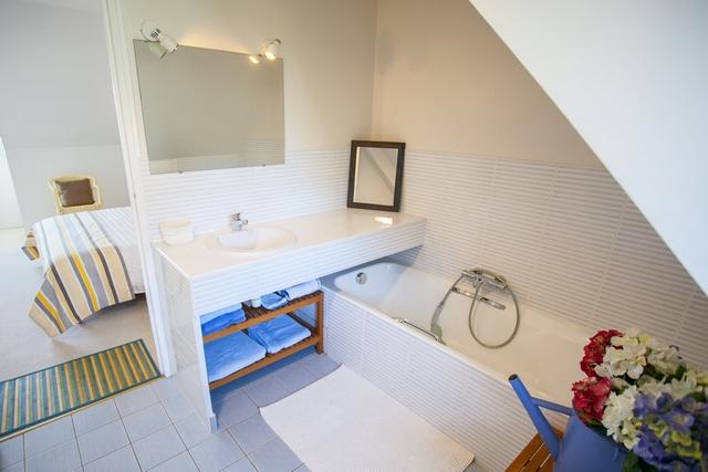 Grande salle de bain équipée d'une baignoire et d'un WC