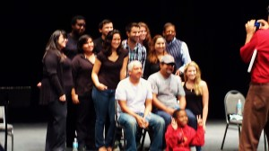 Playwright Mando Alvarado seated (in cap).  Director, Ruben C. Gonzalez seated next to the playwright. Artistic Director of the Black and Latino Playwrights Conference, Eugene Lee (standing in striped vest). Cast and Crew of O(n) THE 5:31 with Cedillo in red taking a picture.
