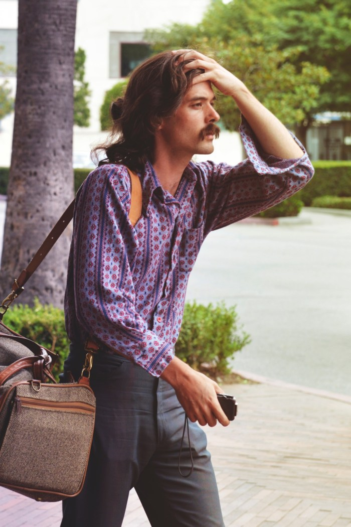 adult bag blur classic facial expression fashion happiness headache hot leisure lifestyle long hair luggage man mustache outdoors park person portrait relaxation summer tired tourist travel traveling wear