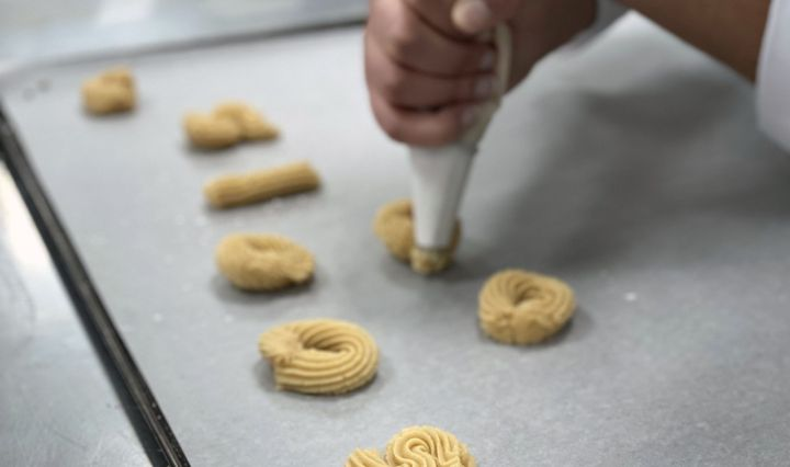 Pastelero elaborando pastas de te con manga pastelera