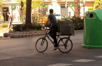 Hombre en su bicicletta en el camino a la siguiente cubo de basura.