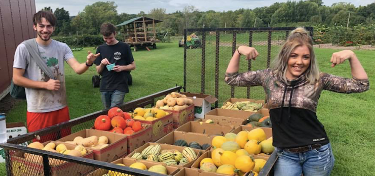 Lagom Landing Gap year students gathering squash at Old Silo Farms, One student flexes her muscle as another laughs. We are stronger with your support!