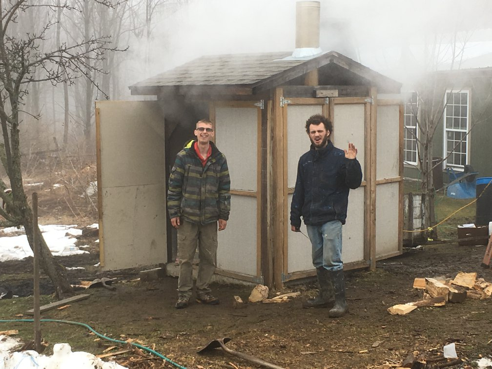 Two young men, students at Lagom Landing gap year, in from of the maple syrup sugar shack.
