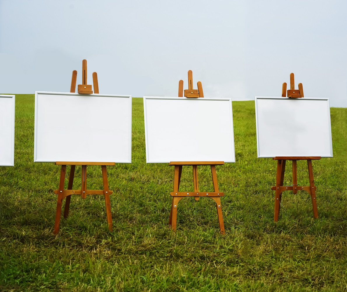 white Blank easel template on green grass meadow background. Wooden easel with white screen on green grass, sunny day outside.