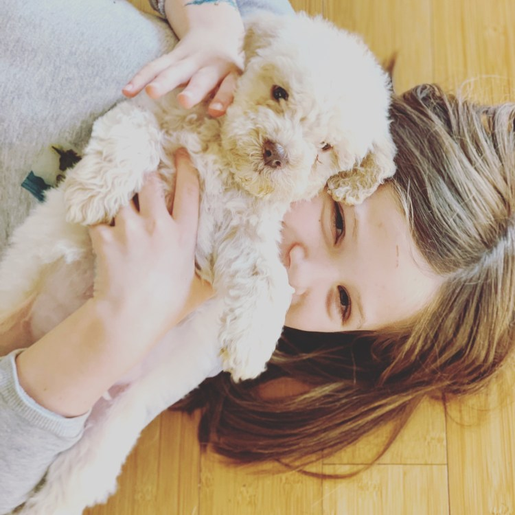 Amico Roma Puppies' oldest daughter on the floor holding a white Lagotto puppy in front of her face while smiling