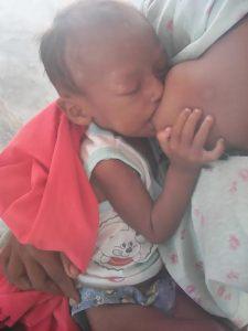 El niño mientras era amamantado por su madre.
