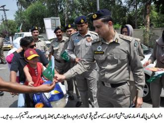 SSP Inkisar Ahmad Khan distributing flags and sweets among road users