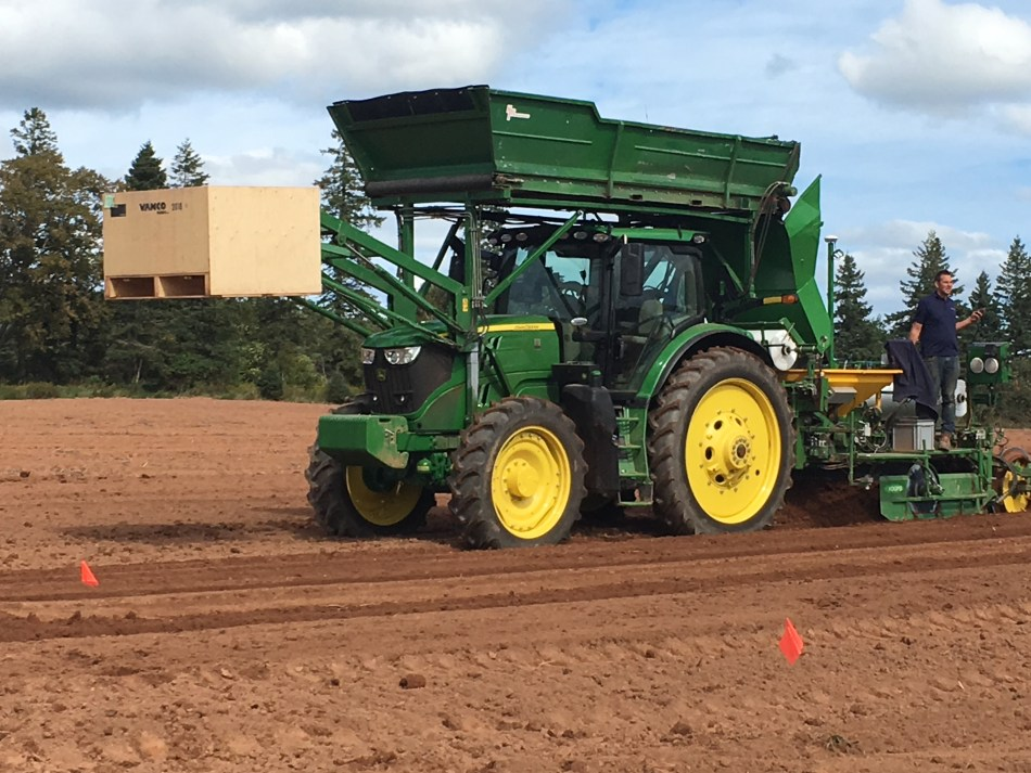 Green tractor with yellow hub caps covered with a bin and holding a big wooden crate.