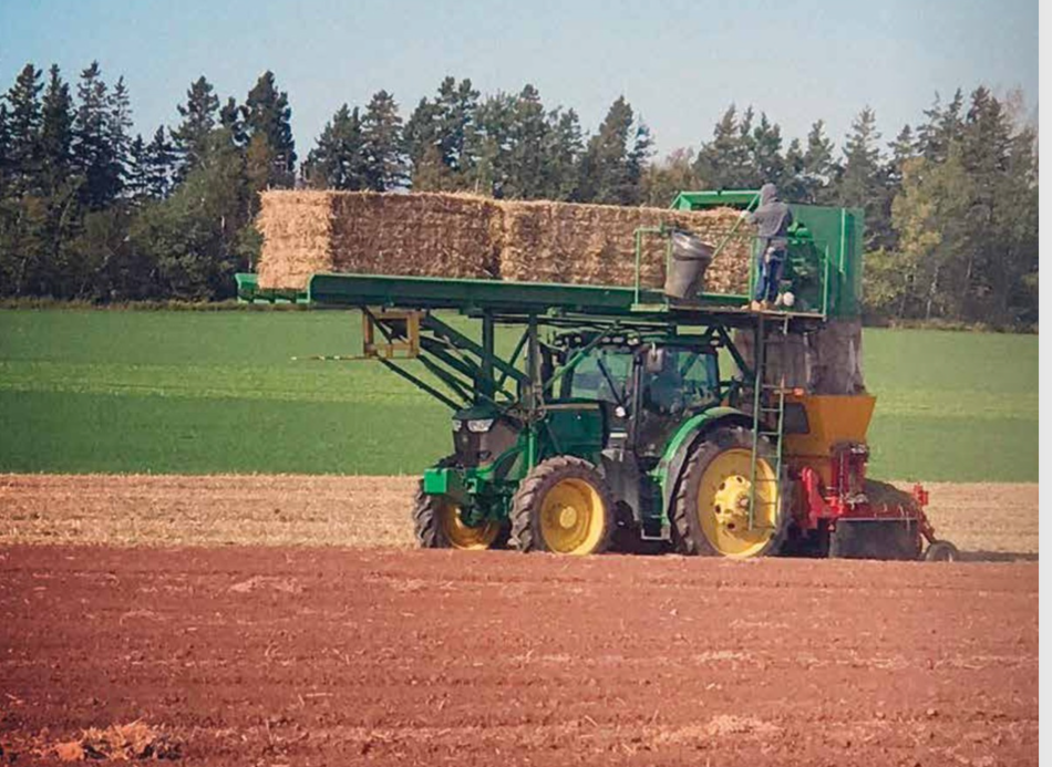 Green tractor with yellow hubs carrying bales of hay on top, empty field.