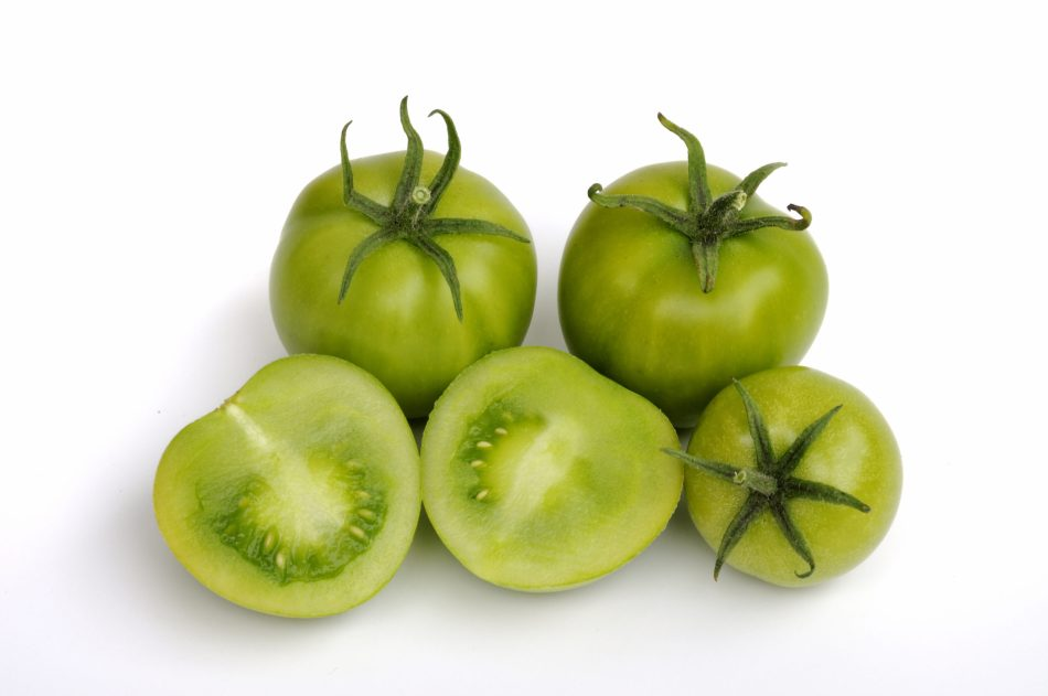 Green tomatoes, one cut open to show the tiny seeds.