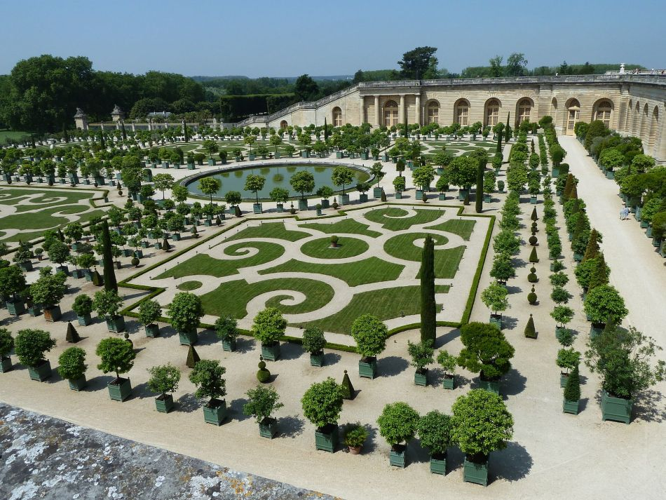Gardens of Versailles with citrus in large pots and orangerie in the background.