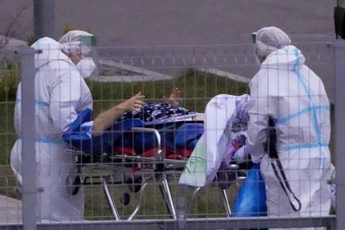 Una persona sospechosa de estar infectada con Covid-19 es ingresada por trabajadores sanitarios en el hospital Kommunarka de Moscú. Foto: Ap