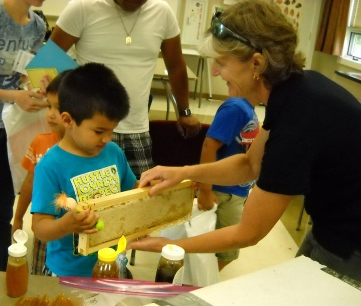 Beth Wilson encourages this young guy to feel the weight of a full frame of honey