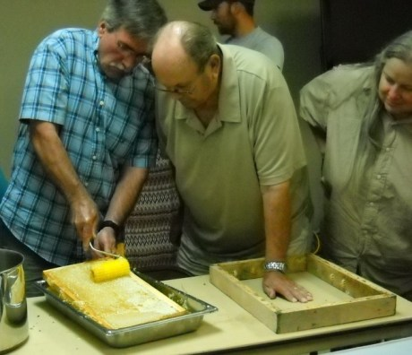 Dan Crockett uses a spiked roller to pierce the cappings of a honey frame, while Imants Rizenbergs watches
