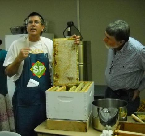 Ray Tucker displays a fully-capped honey frame, ready to be harvested, while Doug Brock looks on