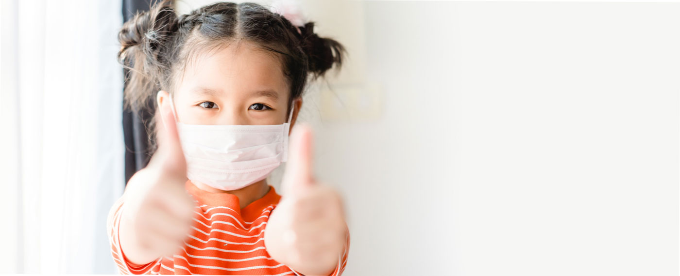 child with mask giving thumbs up