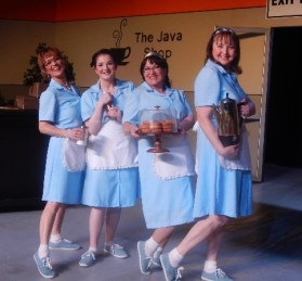 The waitresses of the Java Shop, which is also the Greyhound bus depot, keep coffee cups filled and donuts ready. Maxine (Doris Osinchuk), Josie (Shayla Cameron), Chantico (Dorothy Wuola), and Linda (Velma Hudson) welcome every guest with a smile. In the early morning, Josie practices Patsy Cline songs before anyone else arrives. Then she and Linda prepare for Constable Larsen's burst through the door in search of his first donut of the day.