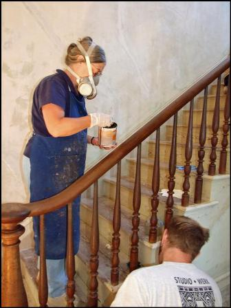Becky Witsell cleans newel and handrail on walnut and oak stairwell