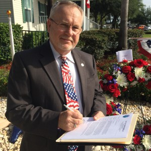 Zephyrhills mayor Gene Whitfield signs a letter to President George H.W. Bush, inviting him to make his next birthday jump in Zephyrhills. (Courtesy of the Greater Zephyrhills Chamber of Commerce)