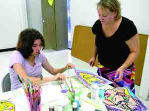 Megan Burgess paints at her weekly art class at the Land O' Lakes Recreation Complex with art teacher Angela Dickerson looking on.  (Michael Hinman/Staff Photo)