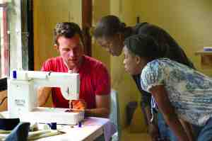 Chris Cox shows Clairsimise Charle and Wislande Felius how to operate a sewing machine that was donated to a sewing center at a vocational school that Cox helped to launch in Haiti. (Courtesy of Chris Cox)
