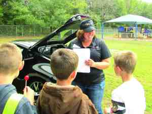 Crystal Enger enjoyed showing off a sports car from Wesley Chapel Nissan to children at Chester Taylor Elementary in Zephyrhills. Enger said the kids seemed to enjoy asking her questions about the car, and she enjoyed seeing them have a chance to think about things they might not have considered before. (B.C. Manion/Staff Photo)