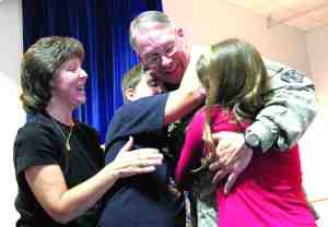 U.S. Army Col. Peter Quinn returns from deployment in Afghanistan just in time for the holidays, surprising his children on stage in front of 200 classmates at Saint Anthony School in San Antonio. The officer's wife Kelly, left, joins him along with two of his children: Gabriel, 13, and Grace, 11.  (Courtesy of Bryant L. Griffin)