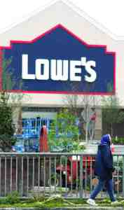 A pedestrian makes her way past the safety fence in front of the new Lowe's store that is aiming to open in April. (Fred Bellet/Photo)