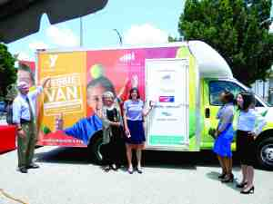 The Veggie Van is a point of pride for Tom Looby, left, president of the Tampa Metropolitan YMCA; Kelley Parris, executive director of the Children's Board of Hillsborough County; Ann Shafer, loan officer at Bank of America; Lakeisha Hood of the Florida Department of Agriculture and Consumer Services; and Michelle Maingot, chairwoman of the YMCA's board of directors. (Kathy Steele/Staff Photos)