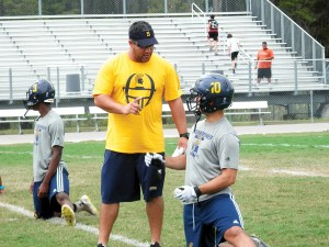 Steinbrenner head coach Andres Perez-Reinaldo talks with linebacker Tyler Mirabella at practice. The defense has helped lead the Warriors to a 4-0 record. (MIchael Murillo/Staff Photo)