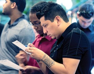 David Angulo of Tampa, foreground, and Javier Perez of Land O' Lakes look over paperwork before applying for a position with one of the new stores opening at Tampa Premium Outlets. Angulo is hoping to obtain a position at the Express Factory or Puma. (Fred Bellet/Photos)