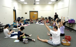 A group of 26 adults and children do a morning stretch at the beginning of the session. Erin and Eric Wheeler lead the Parent, Baby and Yoga class. Despite its name, the class is intended for babies and their caregivers, whether they are parents, grandparents, aunts, uncles or others, Erin Wheeler said. (Steven C. Hollingshead/Photo)