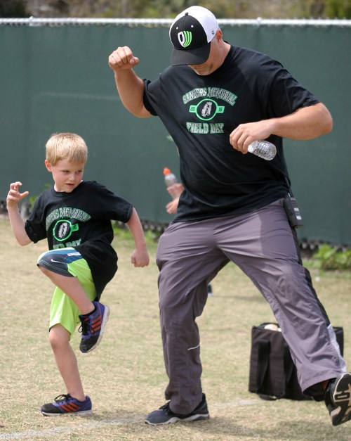 Patrick Mize, 5, works on his pitching form during Field Day activities, with the help of Jason Petry, principal of Sanders Memorial Elementary School.