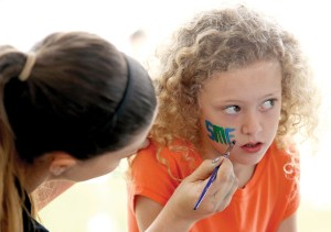 Presley Knouse, 9, has the school's initials painted on her cheek by school art teacher, Kellie Silvey, during the Field Day activities at Sanders Memorial Elementary School. (Fred Bellet/Photos)