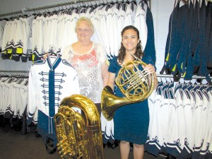 Volunteer Sue Castellano and Pine View Middle School Music Director Amarilys Barbosa stand near some band instruments and uniforms. The school's music programs have grown, and it needs to add more instruments and band uniforms. (File photo)