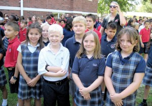 These children are sharing a special moment in history at Saint Anthony Catholic School as they witness the blessing of the school's renovated 1922 building. They are from left in the front row, Sofia Trevino, Andrew Werckman, Cora Woodard and Taylor Young. In the back row, from left are Abigail Kocher, Boden Ballinger, Kyle Bueno and Joseph Hammond.