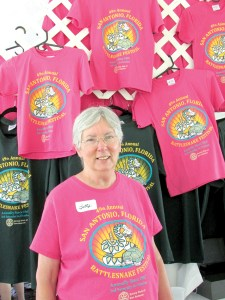 Betty Burke, head of the organizing committee for the San Antonio Rattlesnake Festival, is busy preparing for the festival's two-day 50th anniversary celebration. Here, she is at last year's festival, in front of the event T-shirt tent. (File Photo)