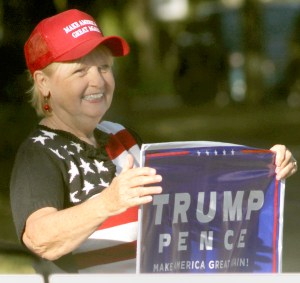 At Precinct 73, Karen Hanzel, a resident of Lexington Oaks , proudly displays a Trump/Pence sign as voters made their way to the polls. (Fred Bellet/Photos)